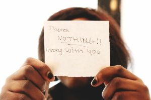 Woman Holding Up a Note That Says There's Nothing Wrong With You