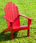 Red Adirondack Chair On A Grass Lawn
